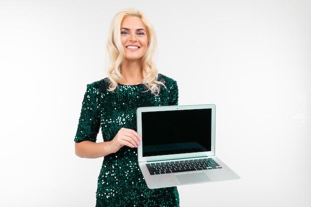 Charmante dame blonde montre un écran d'ordinateur portable vierge sur fond blanc avec copie espace
