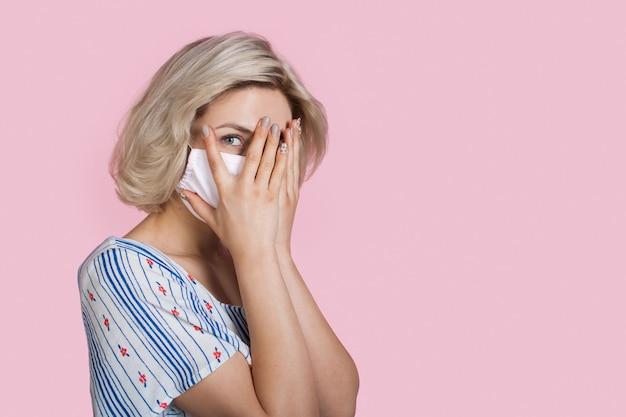 Charmante dame blonde vêtue d'une robe portant un masque médical couvre son visage avec des paumes posant sur un mur de studio rose avec un espace libre
