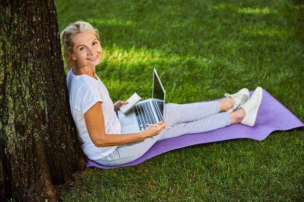 Charmante dame avec un cahier sur ses genoux regardant la caméra et souriant alors qu'elle était assise sur l'herbe verte près de l'arbre