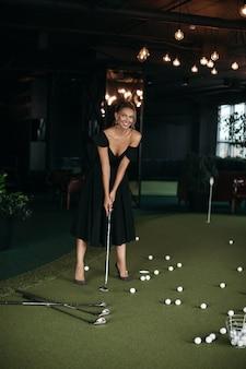 Charmante dame caucasienne pose pour la caméra et joue au golf, image isolée sur fond sombre flou