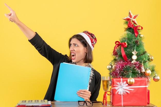 Charmante dame en costume avec chapeau de père noël et décorations de nouvel an tenant le document pointant vers le haut dans le bureau sur jaune isolé
