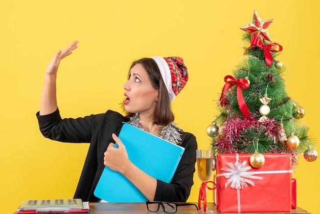Charmante dame en costume avec chapeau de père noël et décorations de nouvel an tenant un document en regardant sa main dans le bureau sur jaune isolé
