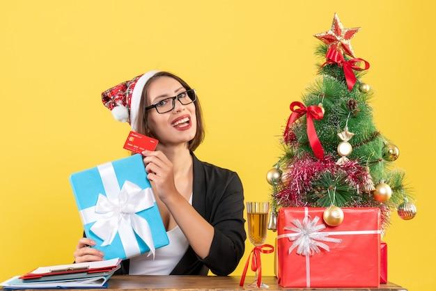 Charmante dame en costume avec chapeau de père noël et lunettes montrant cadeau et carte bancaire au bureau sur jaune isolé