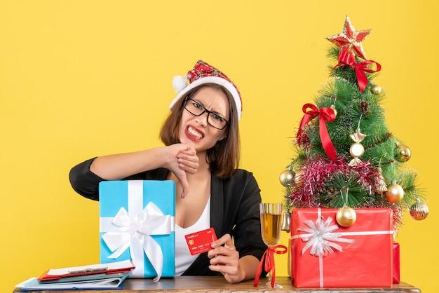 Charmante dame en costume avec chapeau de père noël et lunettes montrant cadeau et carte bancaire faisant un geste négatif au bureau sur isolé jaune