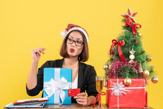 Charmante dame en costume avec chapeau de père noël et lunettes montrant cadeau et carte bancaire pointant derrière dans le bureau sur isolé jaune