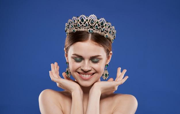 Charmante dame avec une couronne sur sa tête et boucles d'oreilles maquillage fond bleu. photo de haute qualité