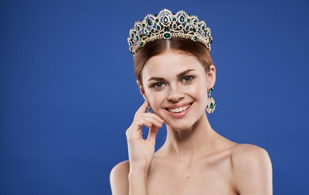 Charmante dame avec une couronne sur la tête et le maquillage des boucles d'oreilles