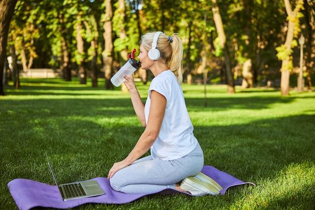 Charmante dame dans des écouteurs sans fil tenant une bouteille de boisson rafraîchissante et souriante assise sur un tapis de yoga avec un ordinateur portable moderne