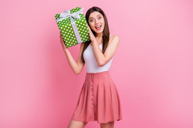 De charmante dame drôle tenir une grande boîte-cadeau verte en pointillé
