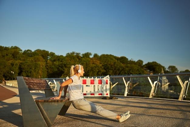 Charmante dame écoutant de la musique avec des écouteurs sans fil et utilisant un banc pendant l'entraînement du matin à l'extérieur
