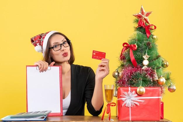 Charmante dame émotionnelle en costume avec chapeau de père noël et lunettes montrant la carte bancaire et le document dans le bureau sur jaune isolé