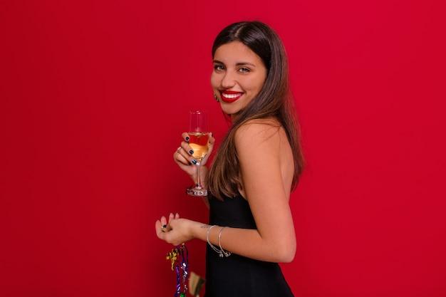 Charmante dame avec grand sourire posant sur un mur rouge avec une coupe de champagne se préparant pour la fête de noël