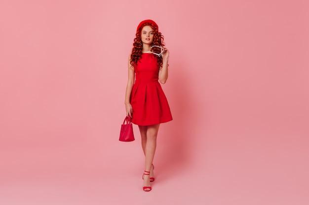 Charmante dame en mini robe rouge, tenant un mini sac à main et des lunettes blanches. fille rousse bouclée en béret posant sur l'espace rose.