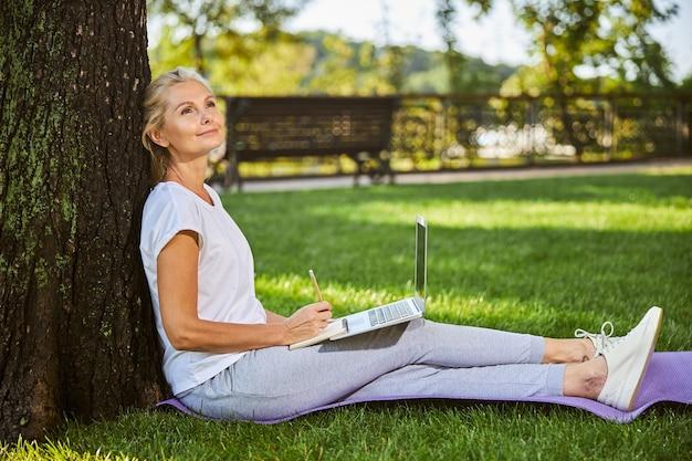 Charmante dame avec un ordinateur portable sur ses genoux tenant un ordinateur portable et souriant tout en se reposant près de l'arbre