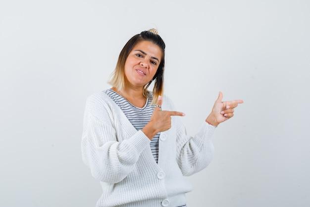 Charmante dame pointant de côté en t-shirt, cardigan et semblant joyeuse