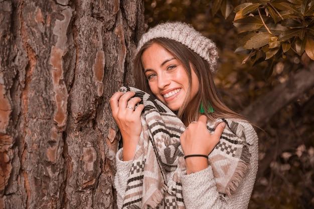 Charmante dame près de tronc d'arbre