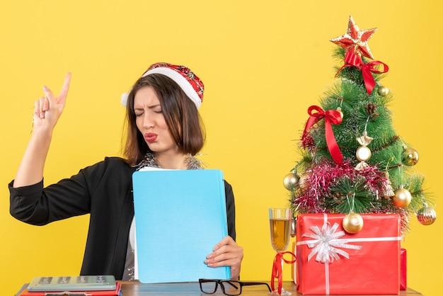 Charmante dame réfléchie en costume avec chapeau de père noël et décorations de nouvel an tenant un document dans le bureau sur isolé jaune
