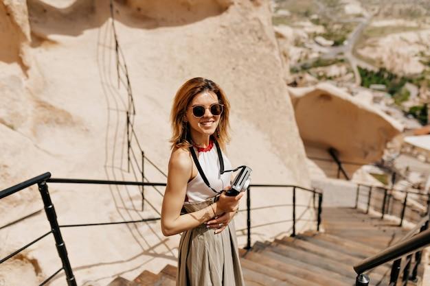 Charmante dame souriante avec une coiffure courte portant des lunettes de soleil tenant un appareil photo rétro et marchant parmi les montagnes au soleil