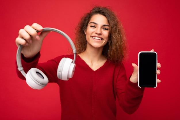 Charmante drôle souriante jeune femme brune bouclée portant un pull rouge foncé isolé sur fond rouge