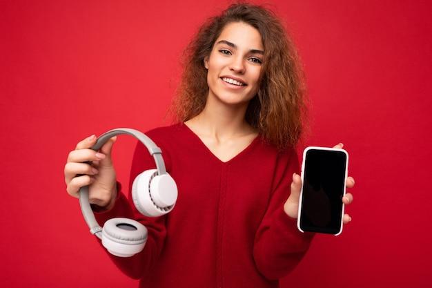 Charmante drôle souriante positive jeune femme brune bouclée portant un pull rouge foncé isolé sur rouge