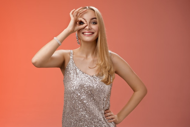 Charmante élégante femme insouciante européenne blonde en robe de soirée scintillante argentée ne montre aucun problème signe correct regarder à travers les yeux souriant ravi de découvrir génial promo intrigué, fond rouge.