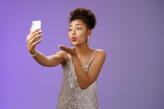 Charmante et élégante jeune étudiante faisant la fête en profitant d'un enregistrement vidéo de bal d'étudiants sur un écran de téléphone à l'apparence d'un smartphone envoyer un baiser d'air soufflant mwah prenant un gadget de prise de selfie, debout sur fond bleu.