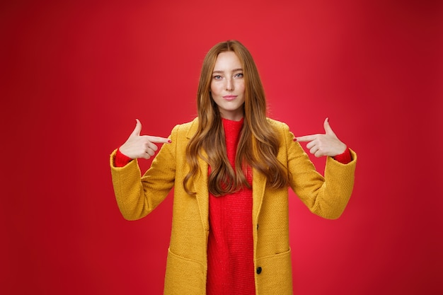 Une charmante entrepreneure, sûre d'elle et optimiste, aux cheveux roux en manteau jaune, se montrant fièrement se vanter de son propre succès ou désireuse d'être candidate souriante et confiante.
