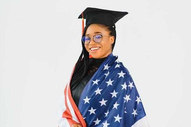 Charmante étudiante souriante à lunettes portant manteau noir et debout avec le drapeau américain