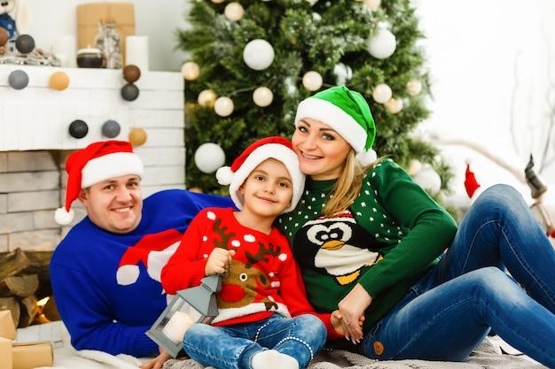 La charmante famille assise près de l'arbre de noël