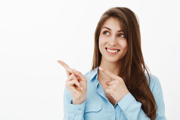 Charmante femme d'affaires brune optimiste posant dans le studio