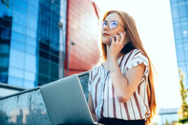 Charmante femme d'affaires caucasienne aux cheveux rouges et taches de rousseur utilise son ordinateur portable tout en ayant une discussion téléphonique