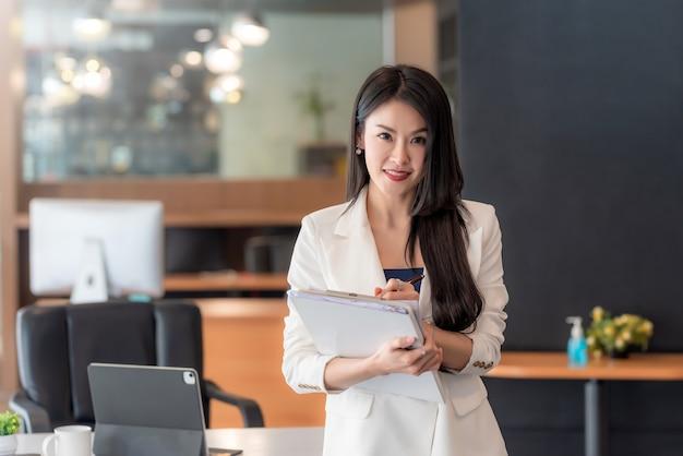 Charmante femme d'affaires debout avec des documents au bureau.