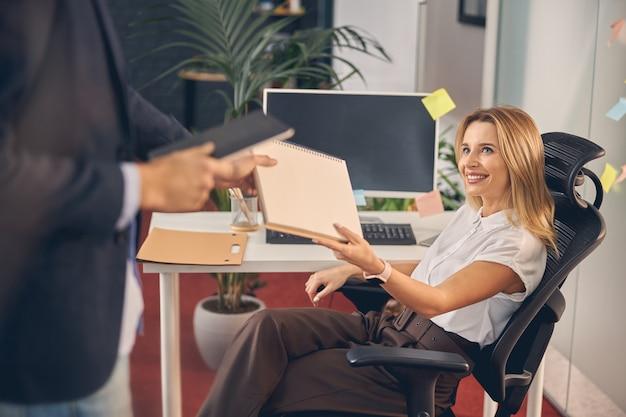 Charmante femme d'affaires regardant un collègue et souriant tout en lui tendant des papiers au bureau