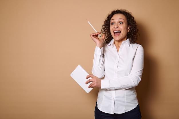Charmante femme afro-américaine bouclée dans une chemise blanche se dresse sur un mur beige avec un stylo et un journal, levant la bouche ouverte exprimant la surprise. copier l'espace