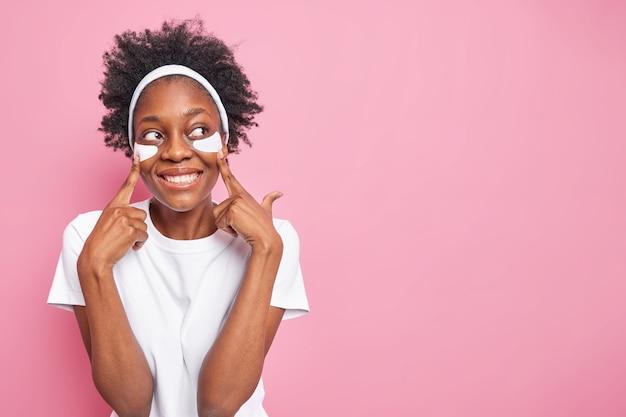 Une charmante femme afro-américaine bouclée et gaie garde les doigts sur les patchs de beauté et regarde volontiers de côté