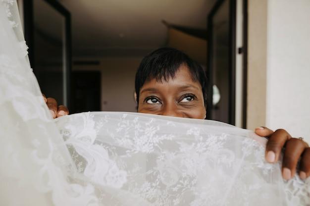 Charmante femme afro-américaine regarde par-dessus la robe de mariée