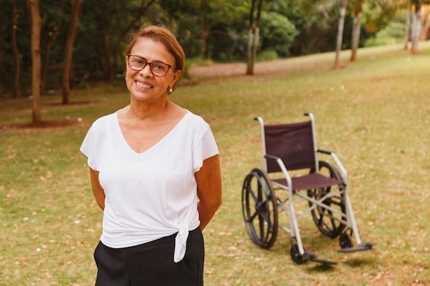 Charmante femme âgée souriant dans le parc debout avec le fauteuil roulant dans le
