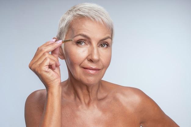 Charmante femme âgée tenant une pince à épiler tout en faisant une nouvelle forme pour les sourcils