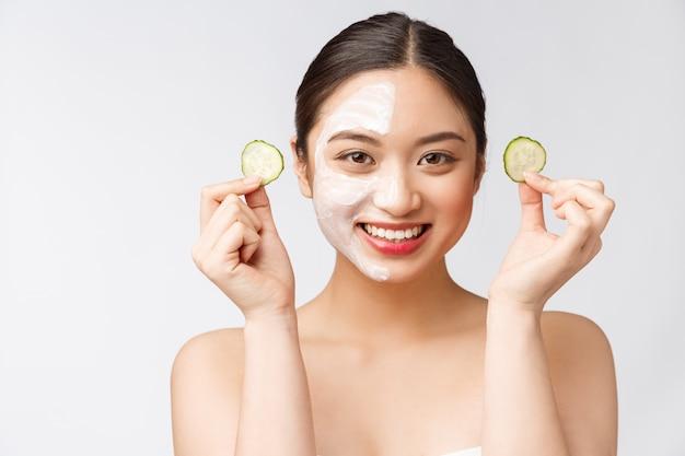 Charmante femme agréable, appliquer la crème sur la moitié du visage