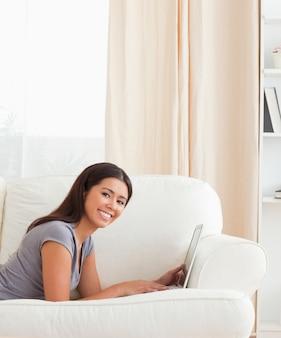 Charmante femme allongée sur le canapé avec ordinateur portable