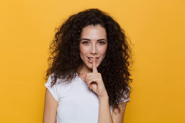 Charmante femme des années 20 aux cheveux bouclés tenant le doigt sur les lèvres isolées sur jaune