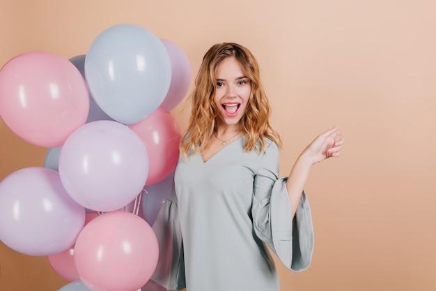 Charmante femme d'anniversaire blonde posant avec plaisir sur un mur léger