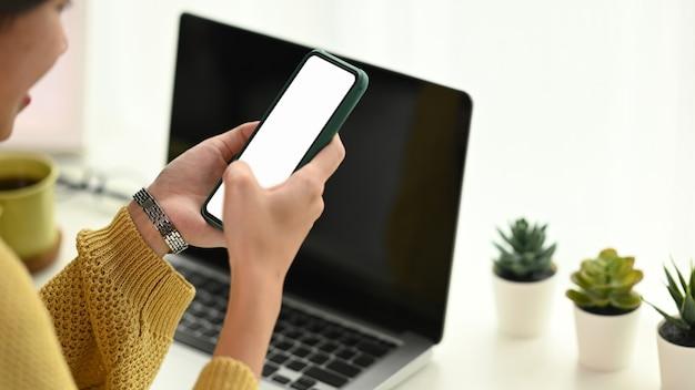 Charmante femme asiatique à l'aide de téléphone portable tout en vous relaxant dans son bureau
