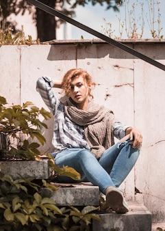 Charmante femme assise sur les marches et réajustement des cheveux