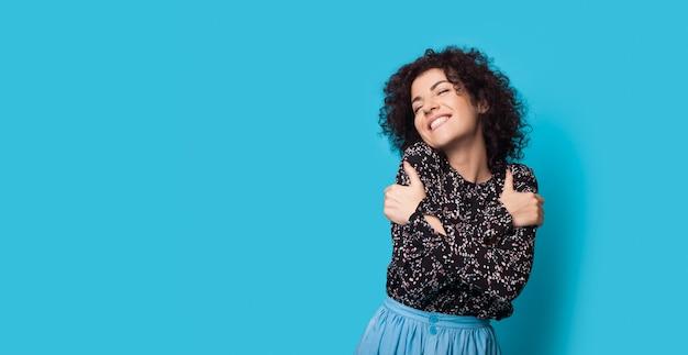Une charmante femme aux cheveux bouclés s'embrasse sur un mur bleu souriant près de l'espace libre