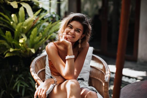 Charmante femme aux cheveux courts en haut brun sourit et regarde à l'extérieur à l'avant