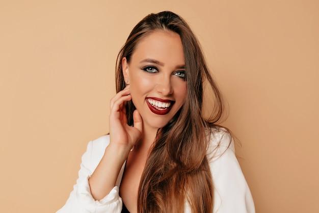 Charmante femme aux grands yeux et sourcils foncés et lèvres de vigne et souriant, un modèle avec un maquillage nude clair, mur beige