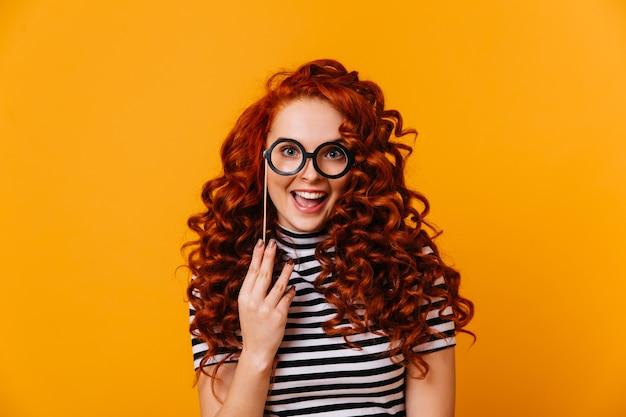 Charmante femme aux yeux bleus et aux cheveux rouges tient le modèle de lunettes et sourit sur l'espace orange.