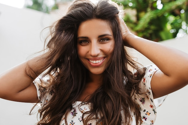 Charmante femme aux yeux verts touche ses longs cheveux noirs et sourit à l'avant sur un mur blanc avec des plantes