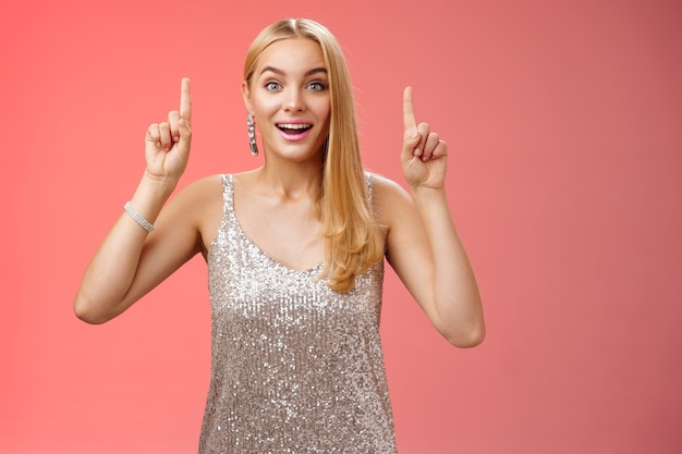 Charmante femme blonde européenne émerveillée dans une fabuleuse robe argentée scintillante lève les mains vers le haut amusée en regardant les étoiles filantes, la caméra de regard de feux d'artifice excitée heureusement surprise, fond rouge.